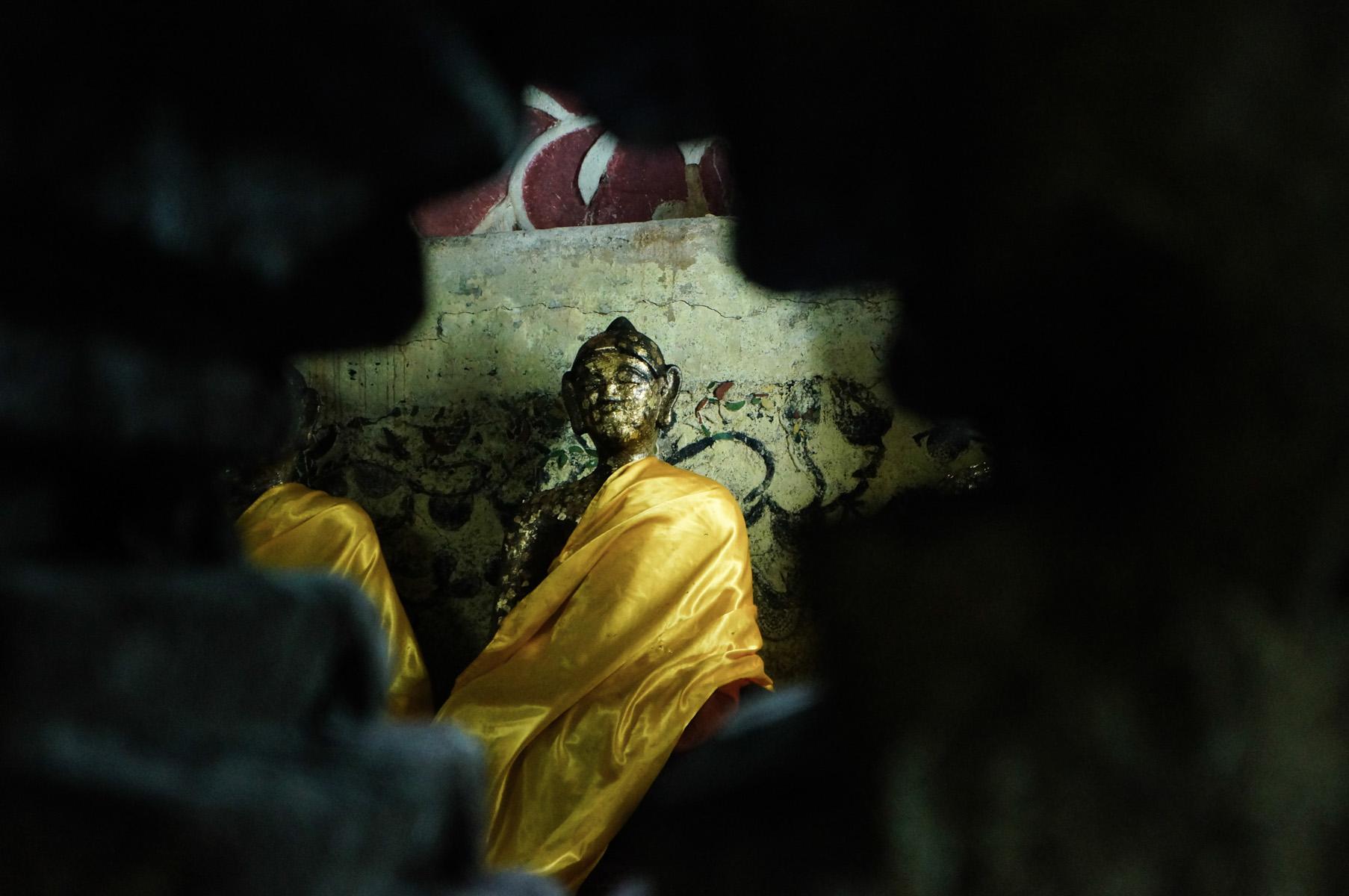 Buddha seen through a port in the wall